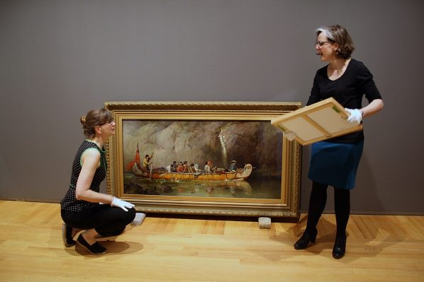 Curators Tobi Bruce and Alicia Boutilier installing Canoe Manned by Voyageurs Passing a Waterfall by Frances Anne Hopkins in The Artist Herself: Self-Portraits by Canadian Historical Women Artists at Agnes Etherington Art Centre.