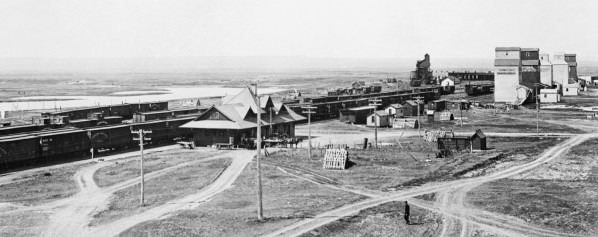 View from town. In this 1916 photo, the roundhouse can just be made out in the background behind the grain elevators. Photo courtesy of the Glenbow Archives.