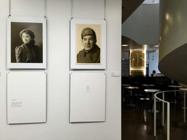 Maude Poissant's show Portraits Égarés hangs in the foreground while the cafe and boutique can be seen behind. On the right, a circular staircase takes you to the library.
